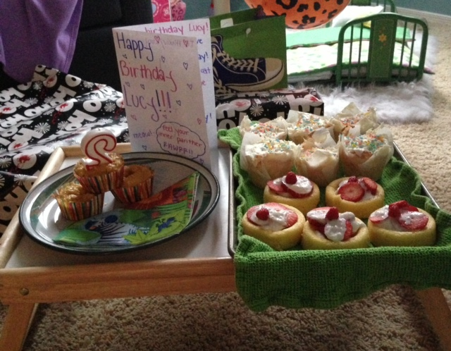 The cat cakes are placed  next to the human strawberry shortcakes and cupcakes.
